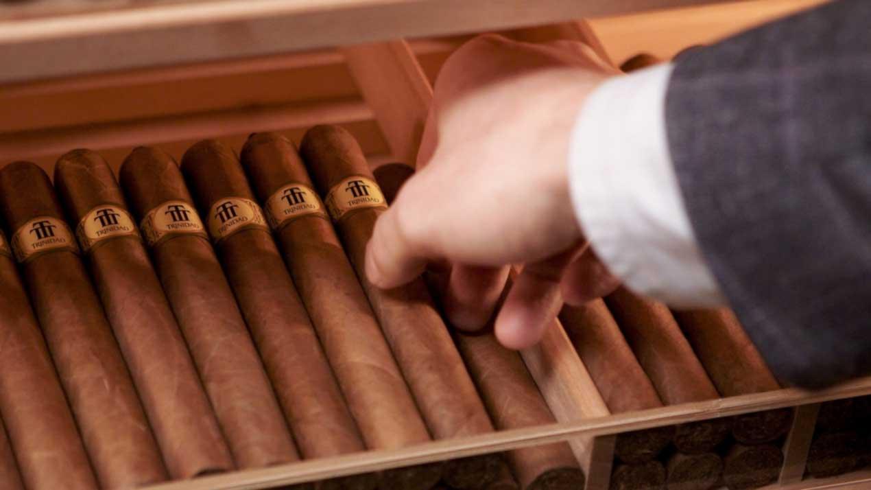 hand selecting cigar from humidor
